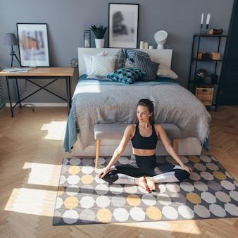 Donna di forma fisica in vestiti di sport che si siede sul pavimento in camera da letto.