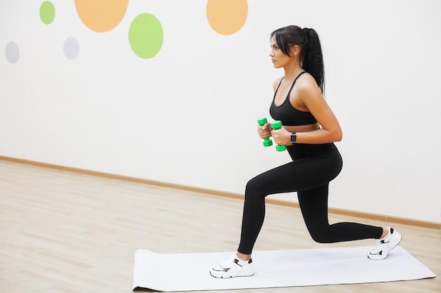 Donna di forma fisica. ragazza di sport in palestra facendo esercizi.