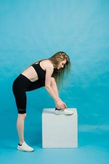 Fitness. donna in abiti sportivi che allunga le gambe, riscaldando sullo spazio blu.