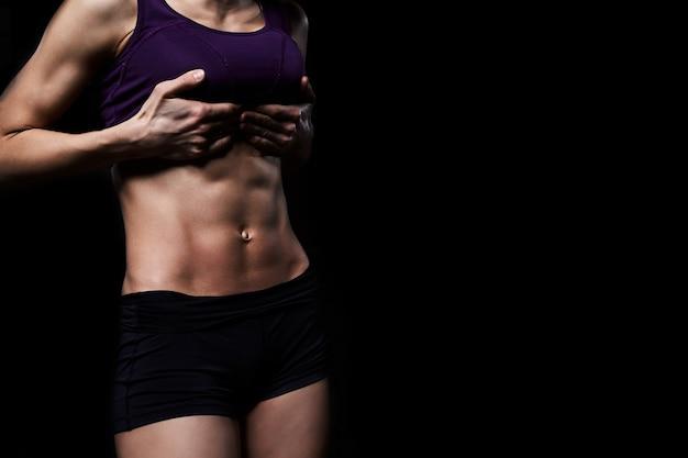 Donna fitness in allenamento forte abs che mostra su uno sfondo scuro.