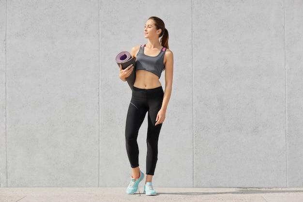 Fitness donna con perfetta forma del corpo, tiene il tappetino per esercizi, va in palestra per allenarsi, indossa scarpe da ginnastica e abbigliamento sportivo, si erge contro il muro di cemento grigio.