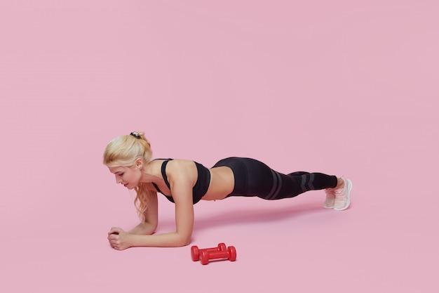 Donna di forma fisica con i muscoli di allenamento corpo perfetto slim e in forma con manubri sulla parete rosa. donna sportiva in abiti sportivi