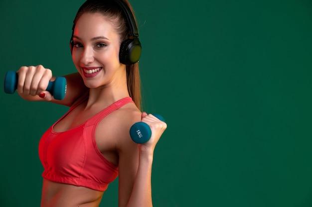 Donna fitness con un corpo forte che fa esercizio con manubri al chiuso e ascolta musica in cuffia