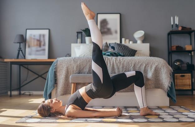Donna fitness che si allena a casa e fa il ponte gluteo a gamba singola.