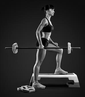 Allenamento della donna fitness con bilanciere in palestra