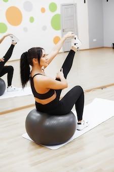 Donna di forma fisica. giovane donna attraente facendo esercizi in palestra.