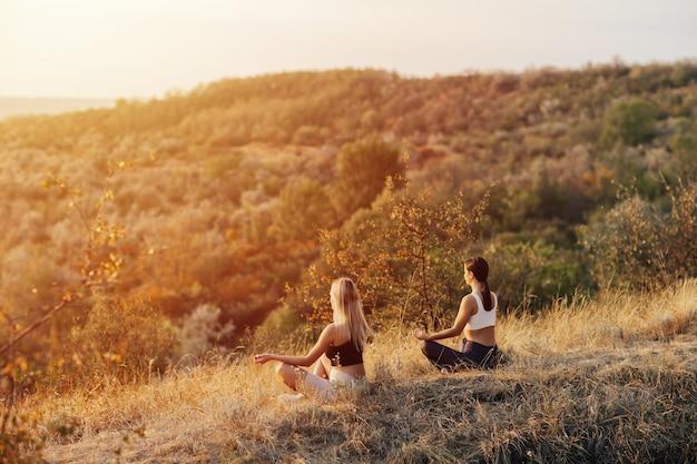 Donne di forma fisica che esercitano esercizi di meditazione yoga dalla foresta. giovani belle donne stanno facendo sport, yoga.