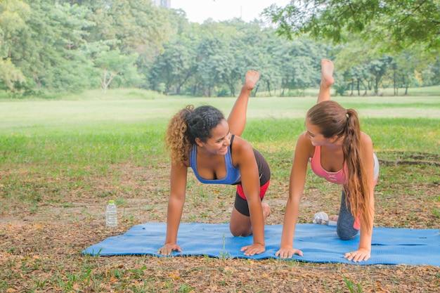 Donne fitness a praticare yoga in un parco. donne che fanno allenamento fitness in un parco.