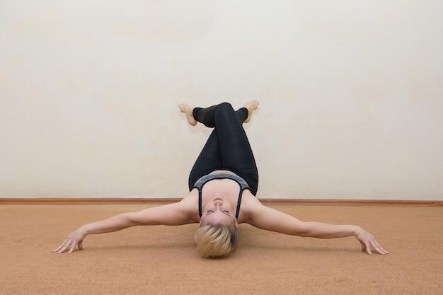 Giovane donna di forma fisica che fa gli esercizi della mano a casa sulla quarantena di autoisolamento