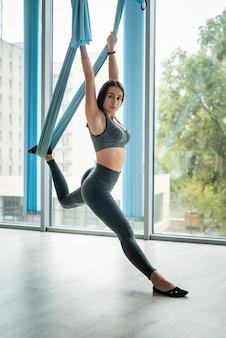 Giovane donna fitness utilizzando amaca blu per fare esercizi di yoga in un club sportivo vicino a windows