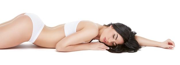 Giovane donna fitness con un bel corpo posa su sfondo bianco.