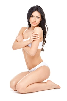 Fitness giovane donna con un bel corpo seduto su sfondo bianco