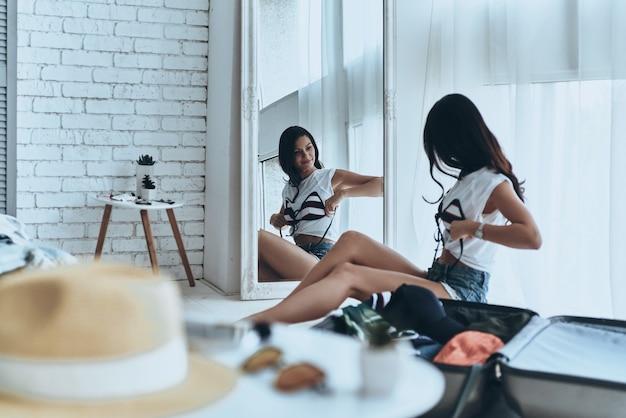 Si adatta perfettamente. attraente giovane donna che prova il suo costume da bagno e sorride mentre si guarda allo specchio a casa