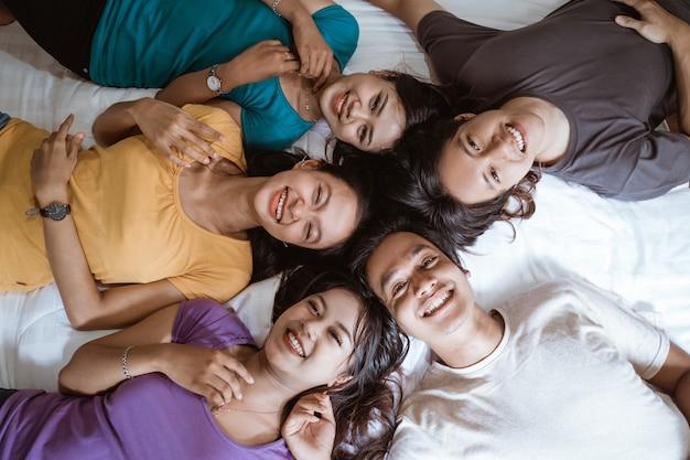 Cinque giovani amici asiatici si divertono insieme in camera da letto ripresi dall'alto mentre sono sdraiati sul letto con la testa insieme