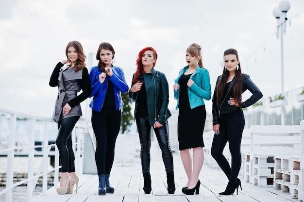 Cinque modelli di belle ragazze giovani a giacche di pelle in posa sul molo