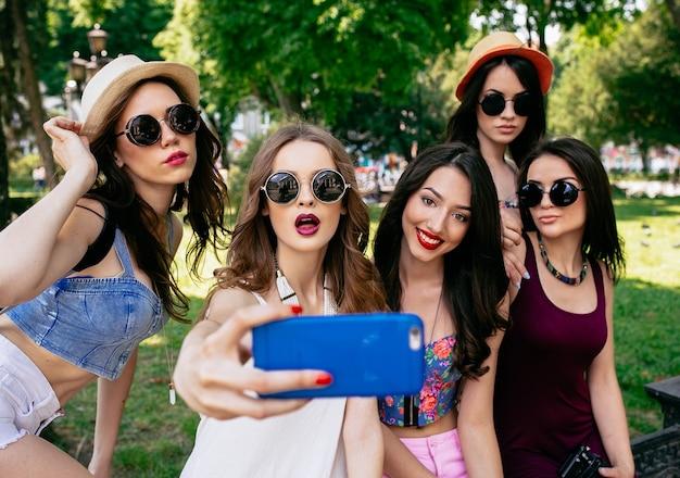 Cinque belle giovani donne fanno selfie nel parco