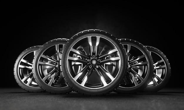 Cinque ruote per auto su asfalto e sfondo nero. rendering 3d
