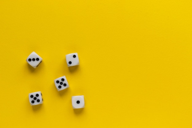Cinque dadi che mostrano lati diversi sulla superficie gialla