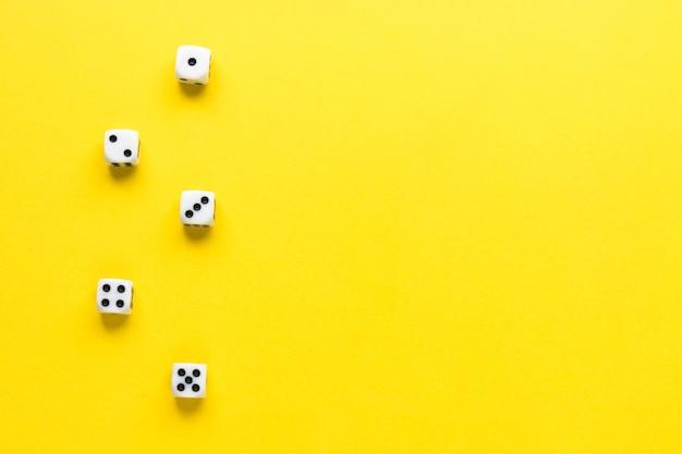 Cinque dadi su sfondo giallo. cubo da gioco con i numeri. articoli per giochi da tavolo. vista dall'alto, piatto. copia spazio.