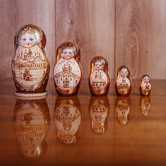 Cinque bambole su un tavolo di legno marrone e una texture su uno sfondo di legno