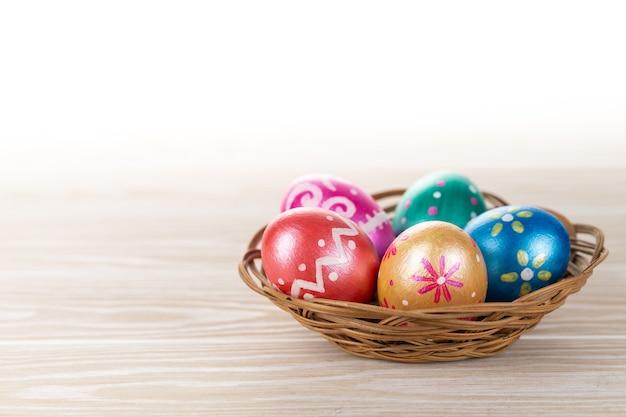 Cinque uova di pasqua alla moda colorate nel cesto decorato in blu intenso, verde, arancione, magenta e dorato su bianco