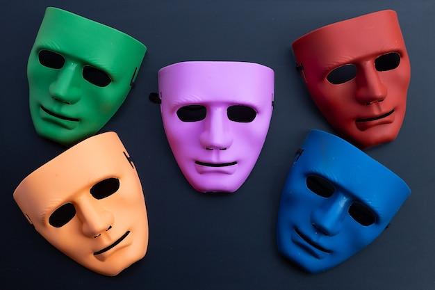 Cinque maschere per il viso sulla superficie scura. vista dall'alto