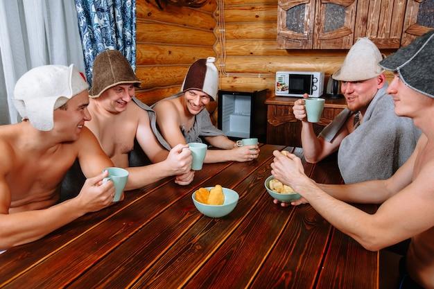 Cinque ragazzi si rilassano nella sauna dopo il bagno turco e bevono il tè