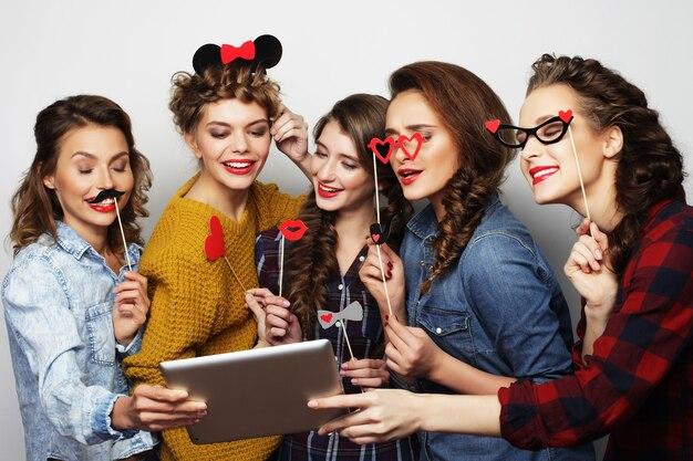 Cinque amiche hipster che si fanno selfie con tavoletta digitale su grigio