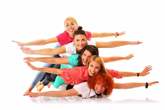 Cinque ragazze gioiose sdraiate l'una sull'altra e sorridenti su bianco