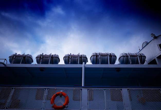 Cinque scialuppa di salvataggio sulla nave sotto il fondo del cielo blu scuro