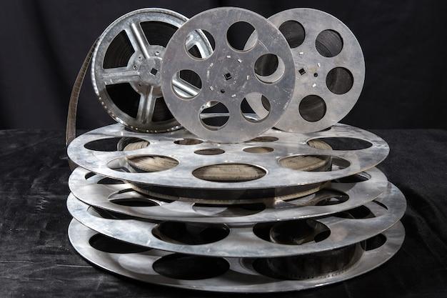 Cinque bobine di film su una superficie nera