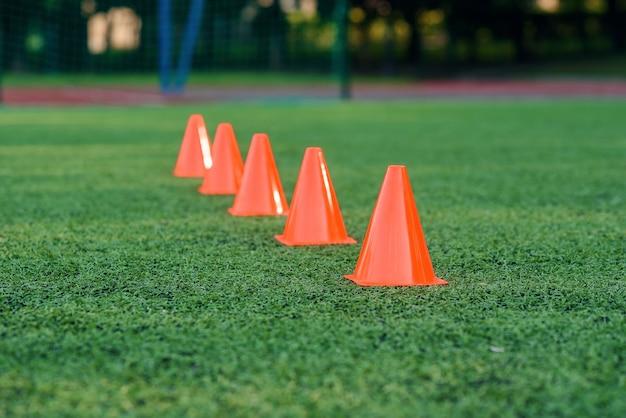 Cinque coni di allenamento arancioni su un campo artificiale di calcio o di calcio verde.