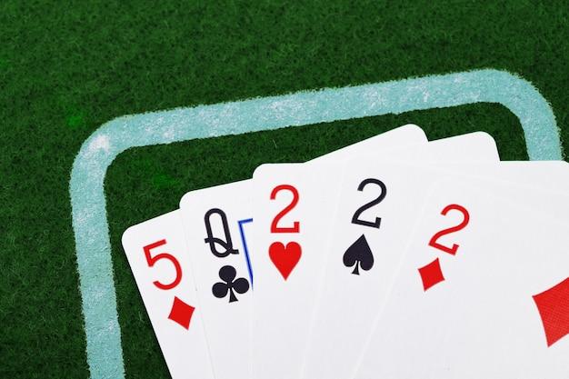 Cinque carte da gioco sulla vista superiore della superficie del tessuto verde