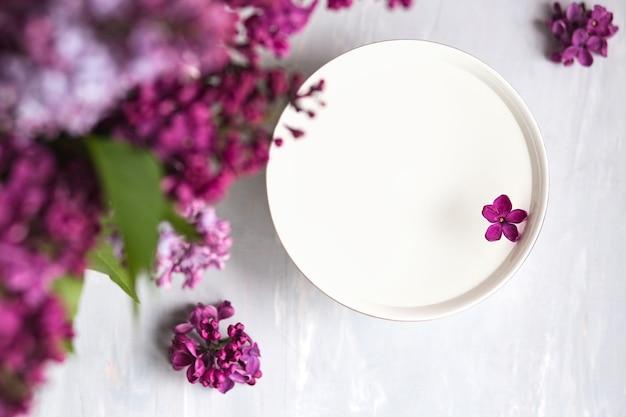 Fiore lilla a cinque punte tra fiori lilla in una tazza con acqua. ripulisci lo spazio per il testo. ramo lilla con fiore a 5 petali.