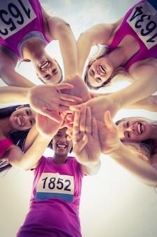 Cinque corridori sorridenti che sostengono la maratona del cancro al seno