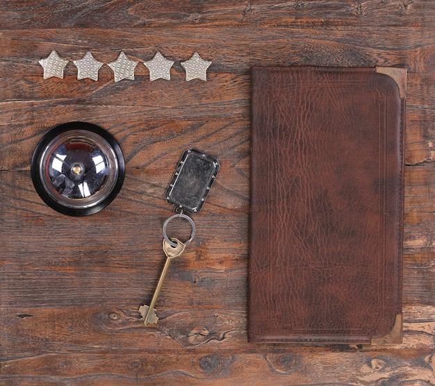 Cinque stelle servizio hotel campana e chiave dell'hotel su un tavolo di legno