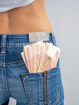 Cinquemila rubli russi banconote nella tasca posteriore dei suoi jeans. il concetto di denaro in tasca. contanti. soldi russi, foto verticale.