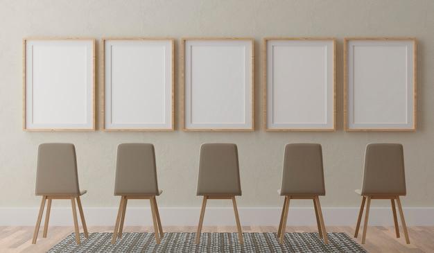 Cinque cornici bianche verticali e sedie sulla parete beige