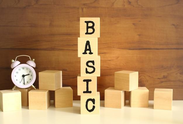 Cinque cubi di legno impilati verticalmente per formare la parola basic su uno sfondo marrone. i cubi sono sparsi nelle vicinanze e c'è un orologio. concetti vista frontale front