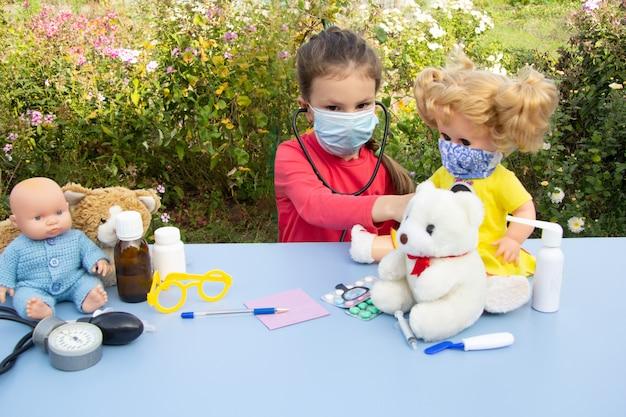 Una bambina di cinque anni in maschera interpreta un dottore per strada. ascolta la bambola.