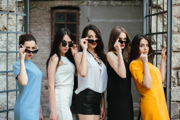 Cinque giovani belle ragazze in posa contro un edificio abbandonato