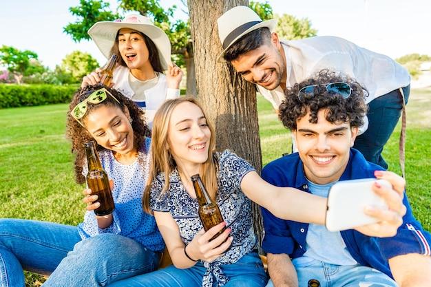 Cinque giovani amici multirazziali che si divertono insieme in un picnic bevendo birra dalla bottiglia