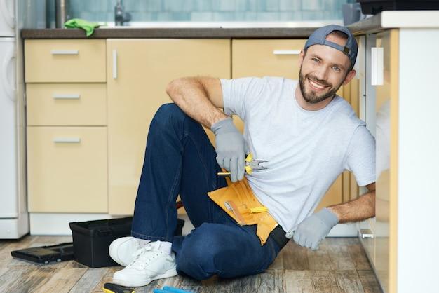 Risolvilo a tutta lunghezza del giovane idraulico tuttofare che indossa la cintura degli attrezzi seduto sul pavimento e