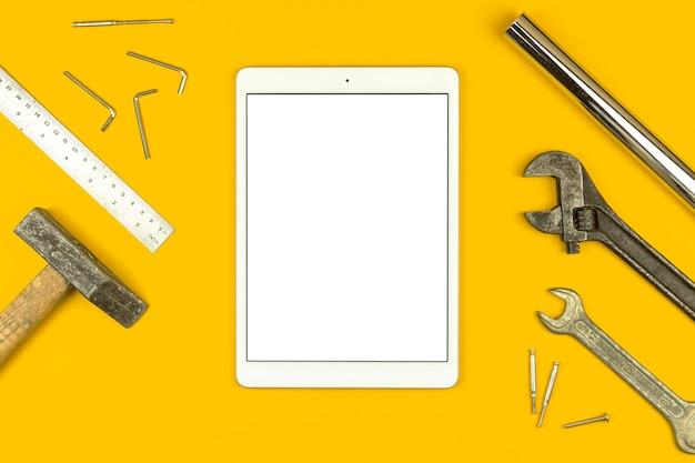 Fissare il concetto di mockup dell'elenco con schermo bianco vuoto del tablet e attrezzatura per utensili, foto piatta e sfondo giallo vista dall'alto, spazio di copia