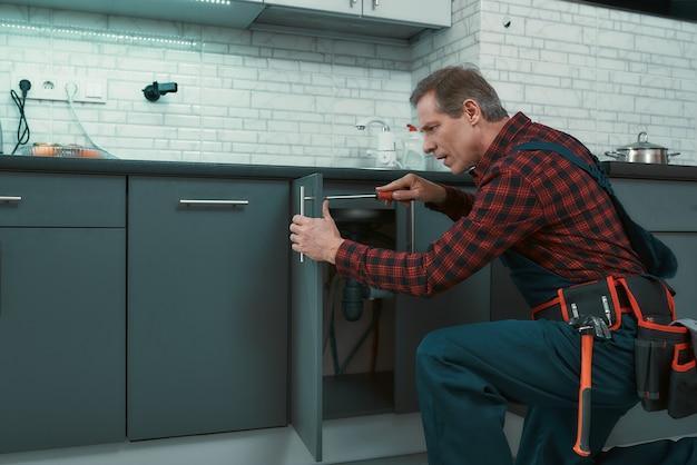 Risolvere tutto l'uomo risolve i problemi domestici uomo maturo che indossa un kit di attrezzi in piedi in cucina