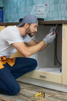 La riparazione delle perdite si è concentrata su un giovane idraulico professionista riparatore che indossa una cintura degli attrezzi accovacciata sul pavimento