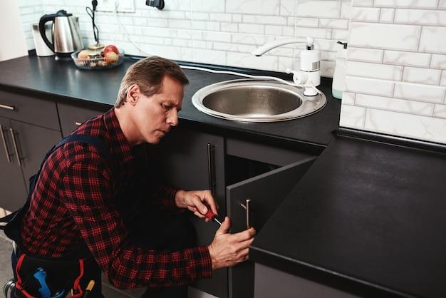 Riparazione del processo del lavandino anziano tuttofare che ripara il lavabo