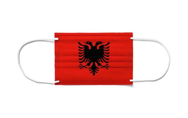 Bandiera dell'albania su una maschera chirurgica monouso. sfondo bianco isolato
