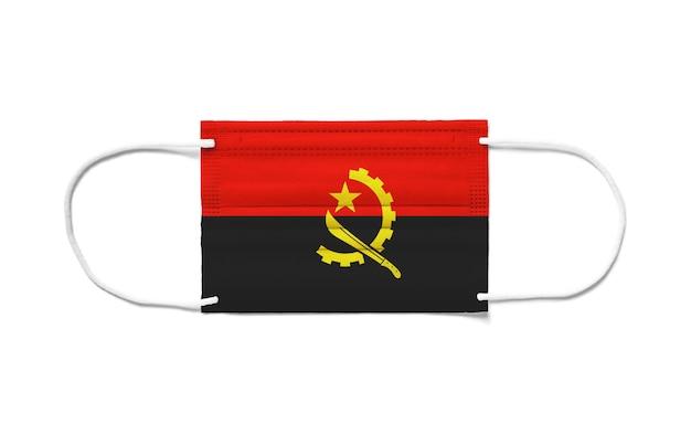 Bandiera dell'angola su una maschera chirurgica monouso. sfondo bianco isolato