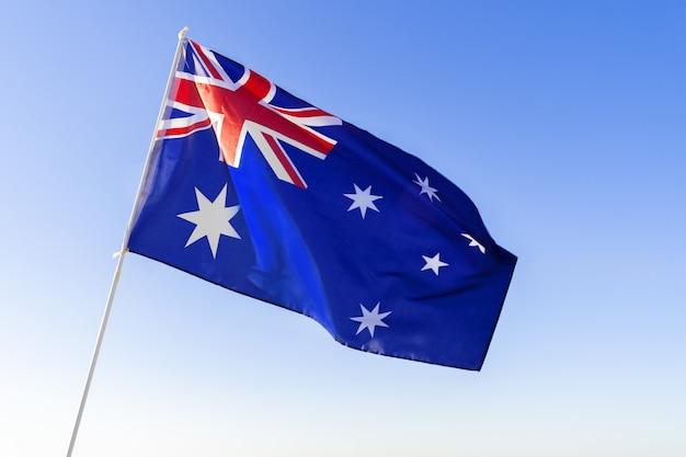 Bandiera dell'australia sventola contro il cielo blu chiaro